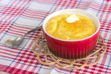 cheese souffle on a red and white cloth in a red bowl Stock Photo