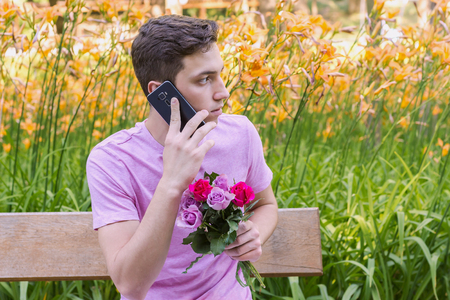 young men waiting date holding mobile phone sitting on a bench with roses Stock Photo