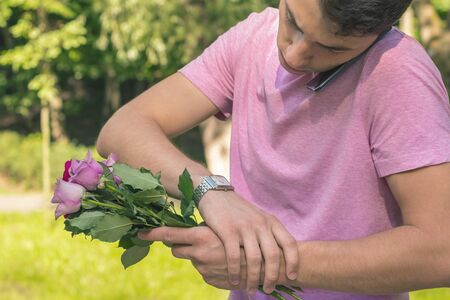 young men waiting date with roses watching time and calling Stock Photo