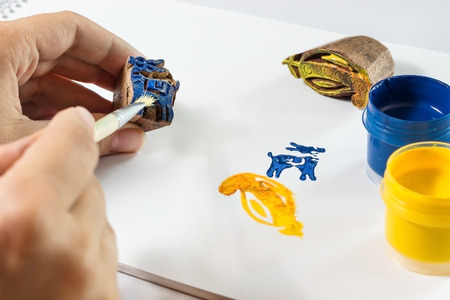 indian stamp blocks composition with hand, paint, brush and paper
