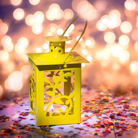 Yellow lantern om a wooden table, bokeh on a background Stock Photo