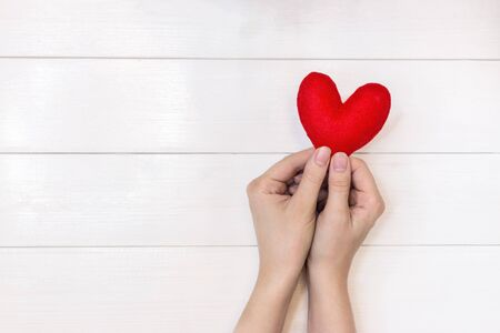 woman hands holding heart figure made from red fabric Stock Photo