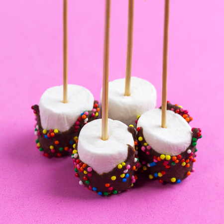 marshmallows on a sticks, laying on pink background. glazed with chocolate and colorful sprinkles.