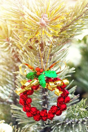 Christmas wreath made from red bells on a fir tree, winter day Stock Photo