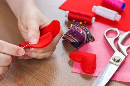 close up  view of hands sewing heart pattern cut from red fabric. sewing tools