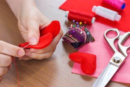 Draufsicht Von Händen Nähen Herz Muster Aus Rotem Stoff ...