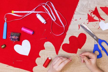 top view of hands sewing heart pattern cut from red fabric. sewing tools Stock Photo