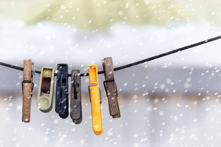 old clothespins on a rope hanging outside house, winter time and snowfall Stock Photo