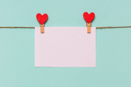 white piece of paper pinned to rope with clothespin decorated with wooden heart