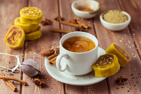 Indian tea masala with spices in white cup, Indian food on wooden table