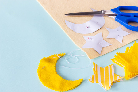 sewing star figures from yellow felt, materials on a light blue background Stock Photo