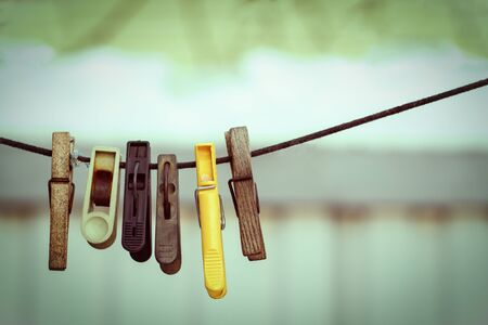 old clothespins on a rope hanging outside house, toned green, vintage look