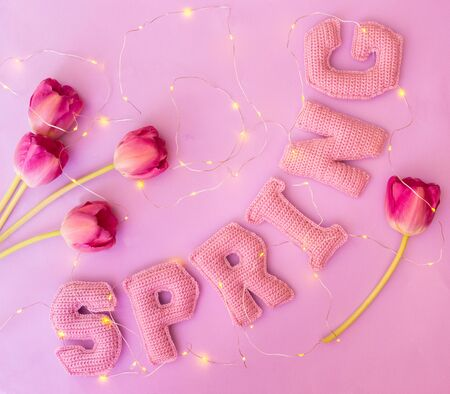 tulip floweres and spring word from knitted letters on pink paper