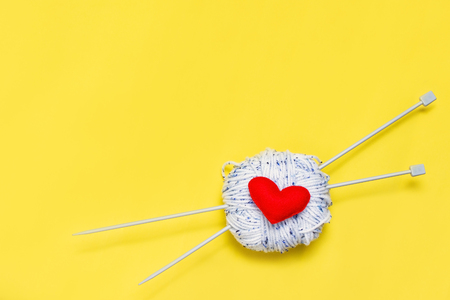 Top view of yarn and red felt heart on yellow background, love to knit image concept