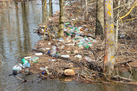 Spring flood of river, plastic trash piled up to trees