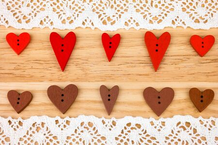 day saint valentin: Wooden red and chocolate hearts on wooden background with lace. Post card for the Valentine. Button love. Wooden buttons. Valentines Day postcard. Wedding invitation.