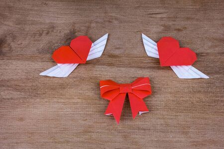 two hearts: Origami hearts with wings on a wooden background. Two hearts.