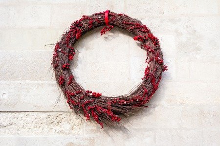 winterberry: Christmas wreath on old wall. Christmas decoration. Red winterberry wreath on rustic background. Stock Photo