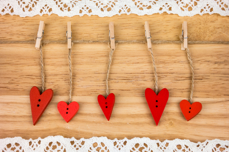 day saint valentin: Wooden hearts on clothespins on wooden background with lace. Stock Photo