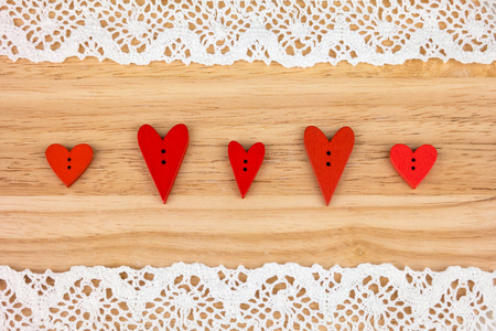day saint valentin: Wooden hearts on wooden background with lace.