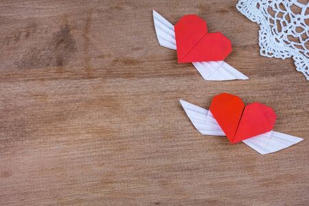two hearts: Origami hearts with wings on a wooden background with lace. Two hearts.