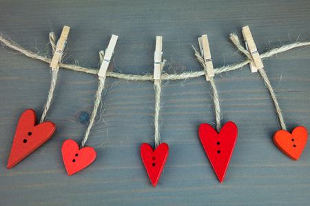 day saint valentin: Wooden hearts on %u0441lothespins on grey wooden background. Stock Photo