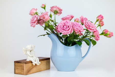 angel roses: Pink flowers in blue jug. Roses in jug. Two angels on wooden banch. Stock Photo