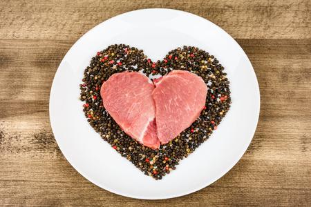 木製の背景にコショウを持つ心臓の形をした生肉。バレンタインデーの贈り物 写真素材