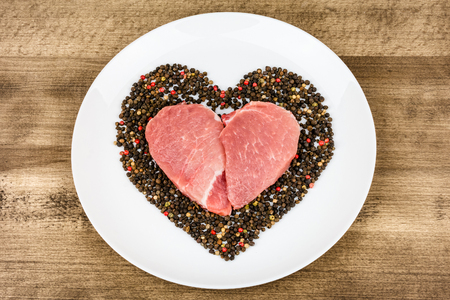Raw meat in the shape of a heart with pepper on wooden background. A gift on Valentines Day.