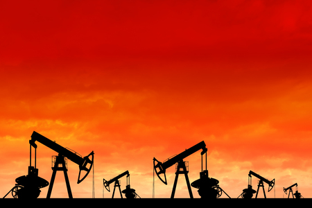 Silhouette of oil pumps at sunset. Oil field at sunset.