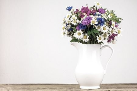 Old photo effect applied. Toned. Wildflowers in white ceramic jug with copy space.