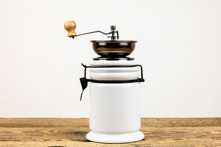 Vintage coffee grinder mill and beans on wooden table photographed over a white background.