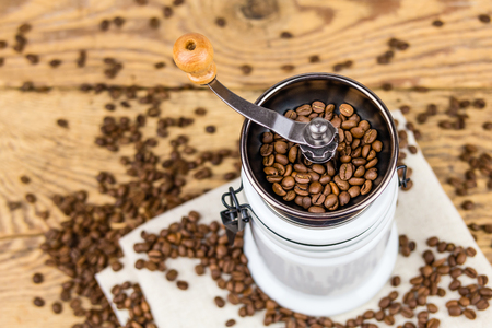 Vintage coffee grinder mill with coffee beans on wooden table . Stock Photo