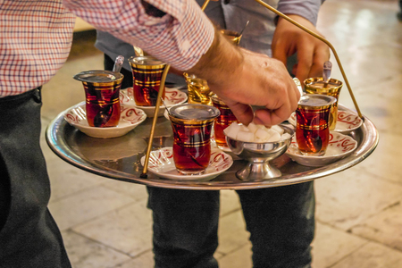 Men's hands is holding a traditional small cups of Turkish black tea on Grand Bazaar in Istanbul.