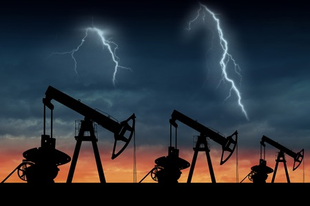 Silhouette of three oil pumps at sunset. Oil field at sunset. Stormy sky with lightning.