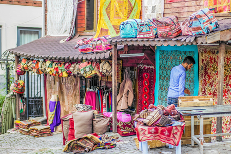 ISTANBUL, TURKEY - November, 2015: Street Life on the streets of Istanbul. Street store with turkish textile bags and colorful carpets.