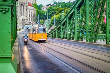 BUDAPEST, HUNGARY - June, 2017: Liberty Bridge or Freedom Bridge and yellow tram in Budapest, Hungary.