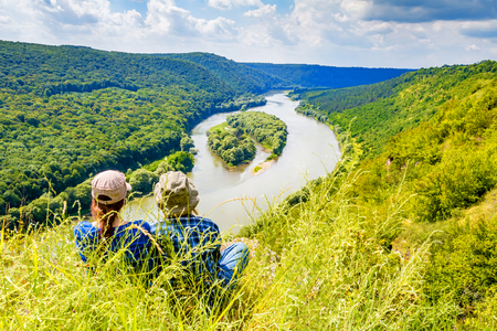 Two girls on a top of mountain above river canyon. Aerial view of Yin and Yang islands on the Dnister River. National Park Dnister Canyon, Ukraine.
