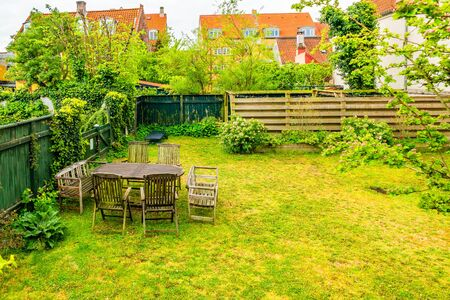Green courtyard with table and chairs in Helsingor, Denmark.