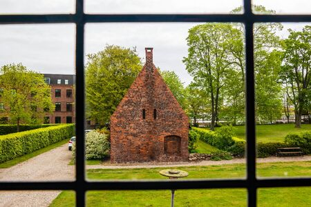 A small house on the courtyard grounds of the church of Saint Mary in the old town of Helsingor in Denmark. Фото со стока