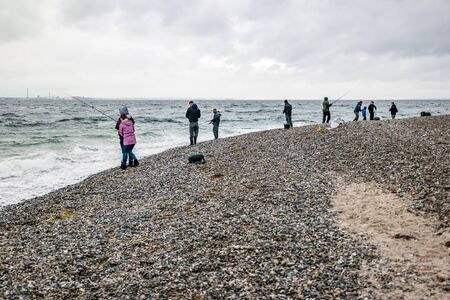 People fishing on danish shore of Oresund, outside the Kronborg castle. Banque d'images