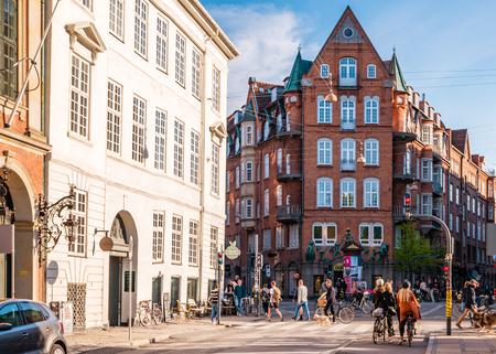 Copenhagen, Denmark - May, 2019: Street life in Copenhagen. People walking, riding bikes in the city center. Редакционное