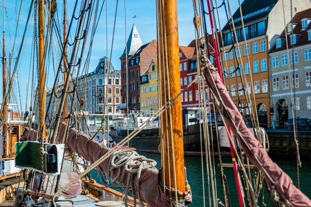 Copenhagen, Denmark - May, 2019: View of Nyhavn pier with color buildings, ships, yachts and other boats in the Old Town of Copenhagen, Denmark.