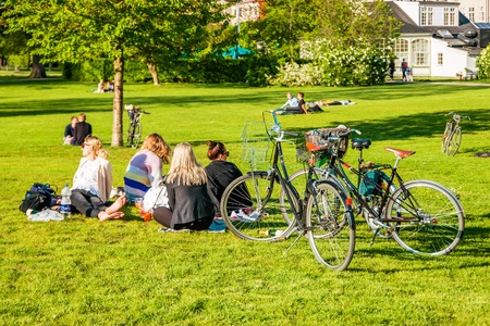Copenhagen, Denmark - May, 2019: People relaxing at the Kings garden next to Rosenborg castle.