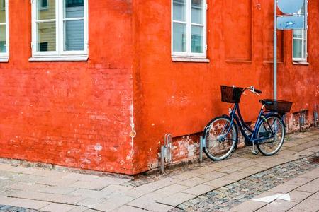 Helsingor, Denmark - May, 2019: Exterior architecture. Bicycles in front of orange facace in Helsingor, Denmark.