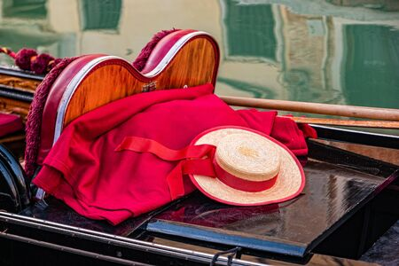 A close up of a gondola with oars, gondolier hat and red blanket in Venice, Italy.