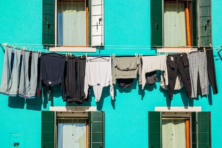 Typical colorful house of Burano Island with hanging laundry at its facade 版權商用圖片