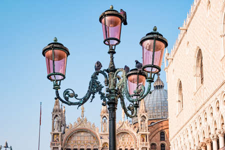 Famous venetian street lamps with pink glass in front of Basilica di San Marco in Venice, Italy.