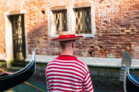 Gondolier in gondolier hat on canal street in Venice, Italy. Standard-Bild