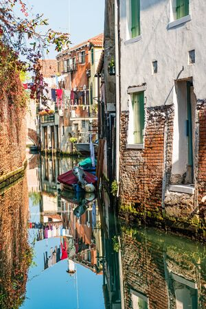 Traditional canal street with reflection in the water laundry hanging out of a typical Venetian facade. Italy.